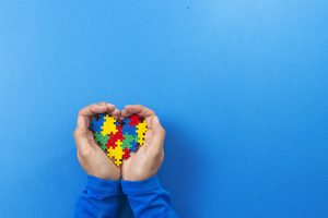 World autism awareness day concept. Child hands holding colorful puzzle heart on blue background DOCU_GRUPO