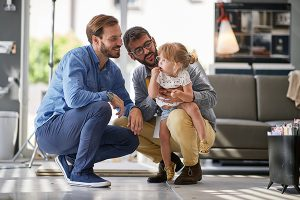 gay parents with child in store for household
